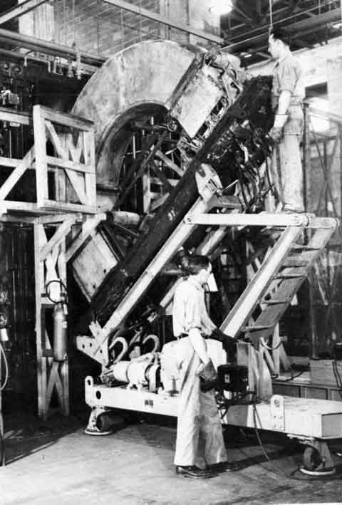 "D-Unit Loading Operation. Loading handlers are using a loading dolly to install a calutron. Calutrons were referred to as ""D-Units"" during the war, not as calutrons."