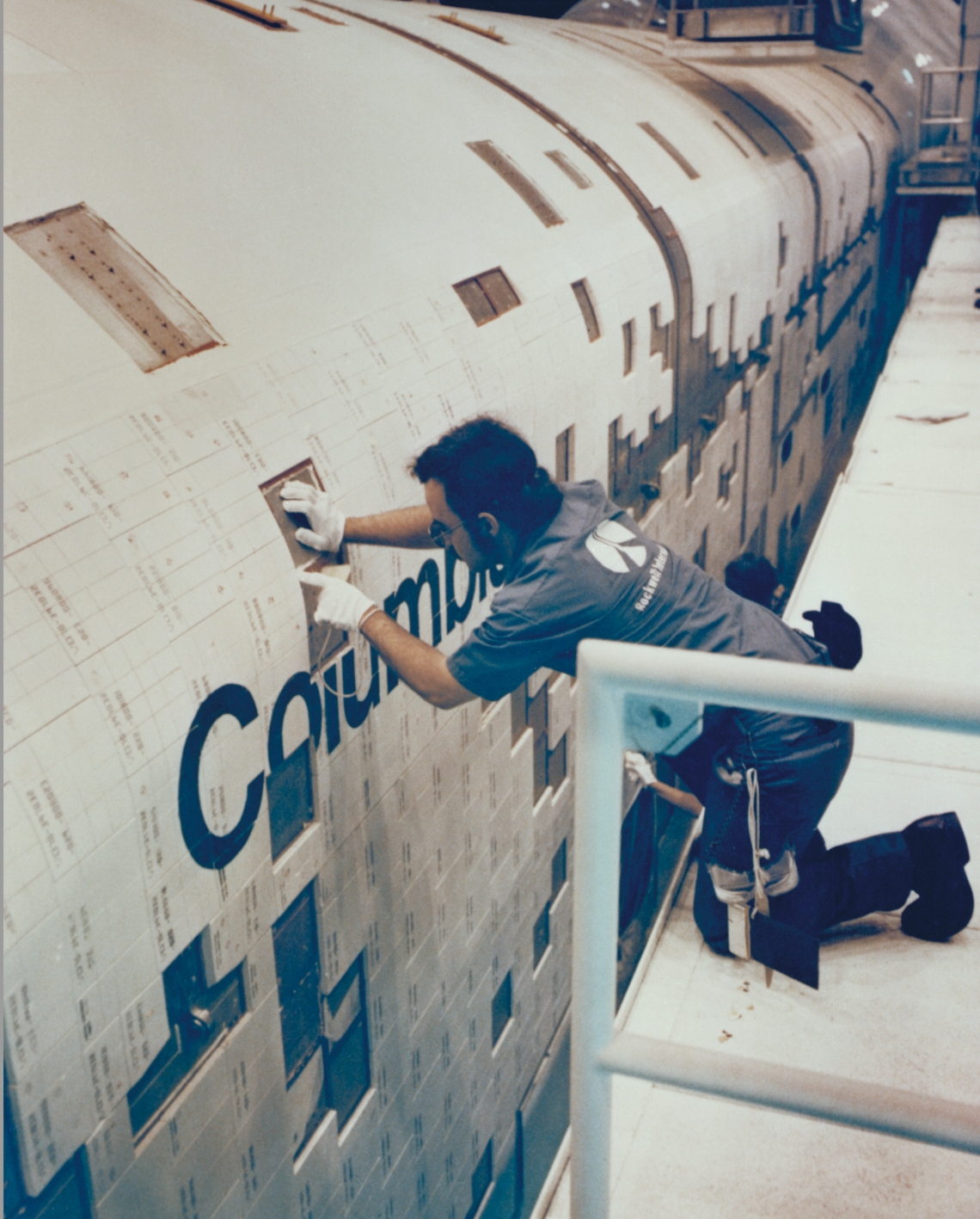 A technician mounting a thermal protection tile on the Space Shuttle Columbia in 1980, around 20 years before Eva started work as a tile technician. (Photo credit: NASA)