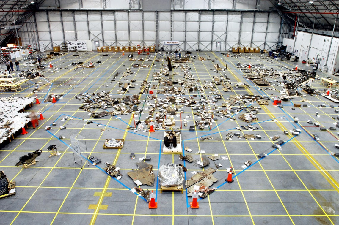 An overview of the Columbia debris hangar showing the orbiter outline on the floor with some of the 78,760 pieces that had been identified when the photo was taken in 2003.