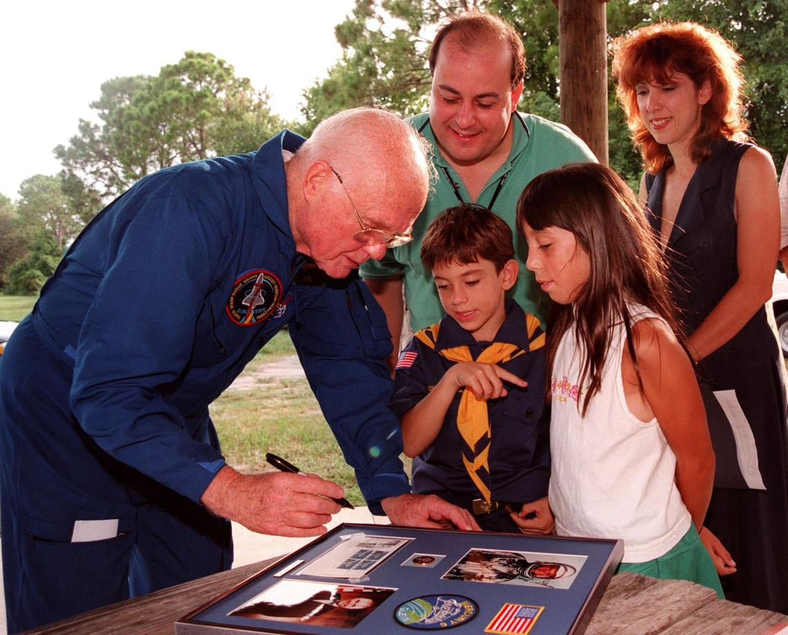 Astronaut John H. Glenn Jr. autographs a photo for Eva's two children