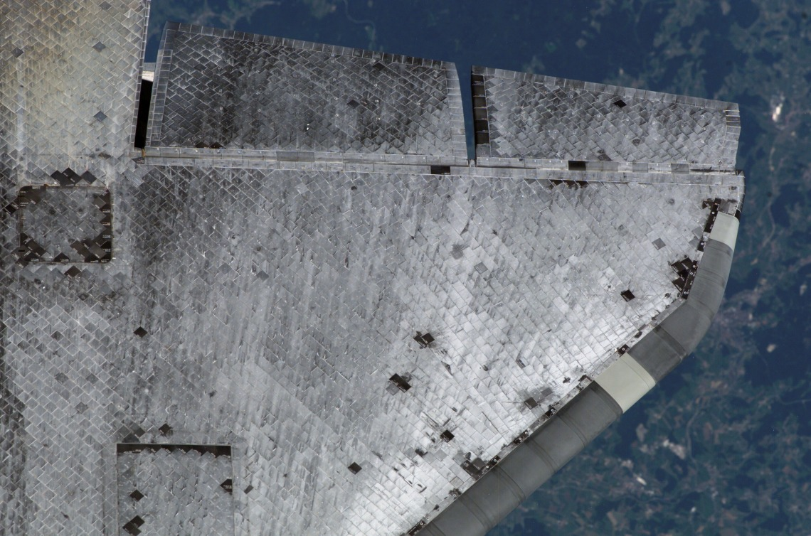 The underside of the Space Shuttle's wing showing the Thermal Protection System tiles during flight.